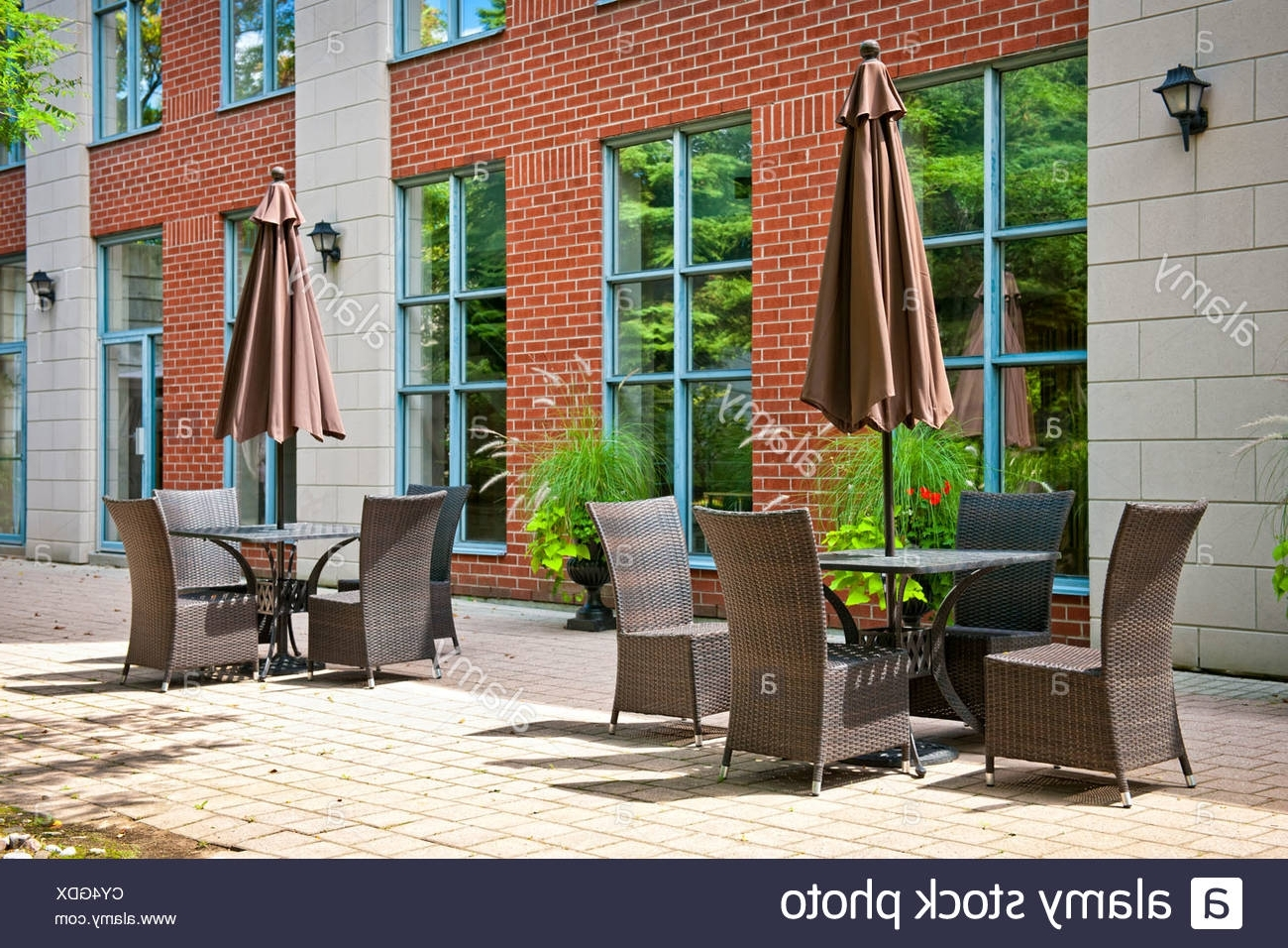 Best And Newest Patio Furniture With Umbrellas On Stone Patio Near Upscale Condo Intended For Upscale Patio Umbrellas (Gallery 17 of 20)