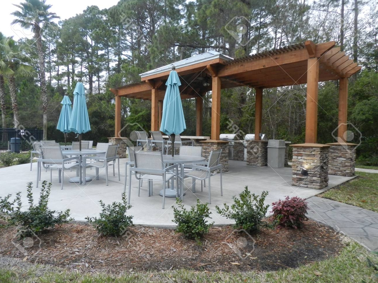 Patio Furniture With Umbrellas On Stone Patio Near Upscale Condo With 2019 Upscale Patio Umbrellas (View 16 of 20)