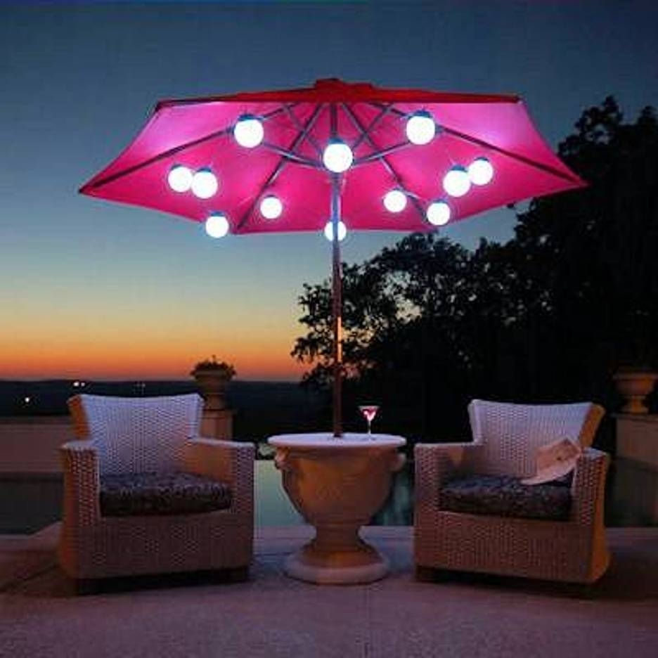 Patio Umbrella Marquee Lights White Wicker Chair Scene At Night Inside Preferred Patio Umbrellas With Lights (View 11 of 20)