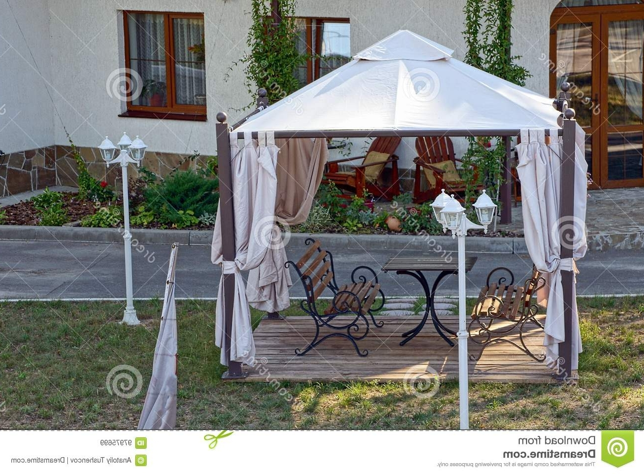 Well Known Outdoor Gazebo Lanterns Pertaining To Open Gazebo With Benches On The Lawn With Lanterns Near The Road (View 4 of 20)