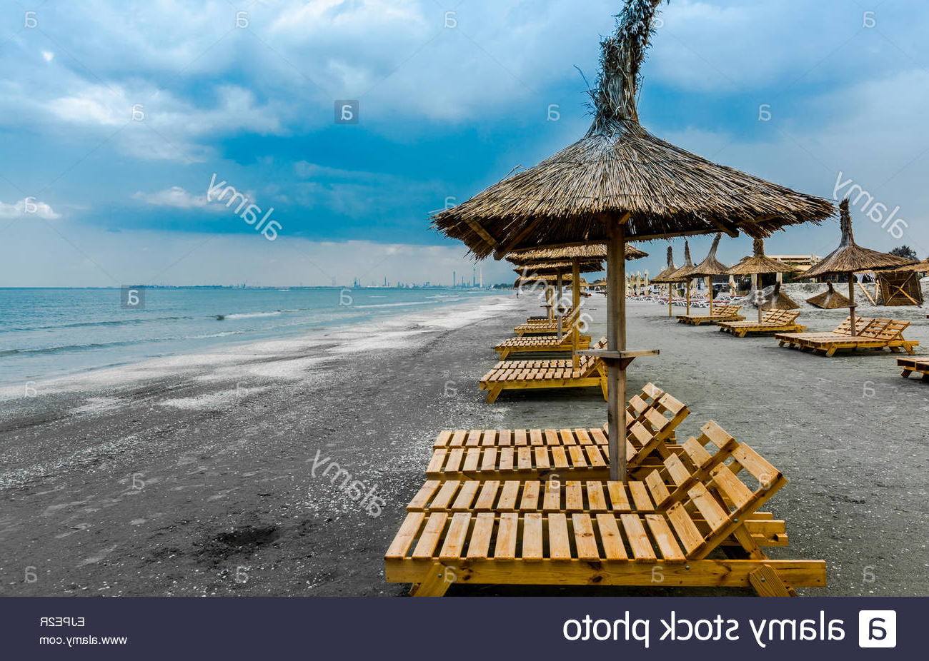 Cloudy Seaside Beach With Wooden Lounge Chairs And Straw Umbrellas With Regard To Popular Seaside Beach Umbrellas (View 2 of 20)