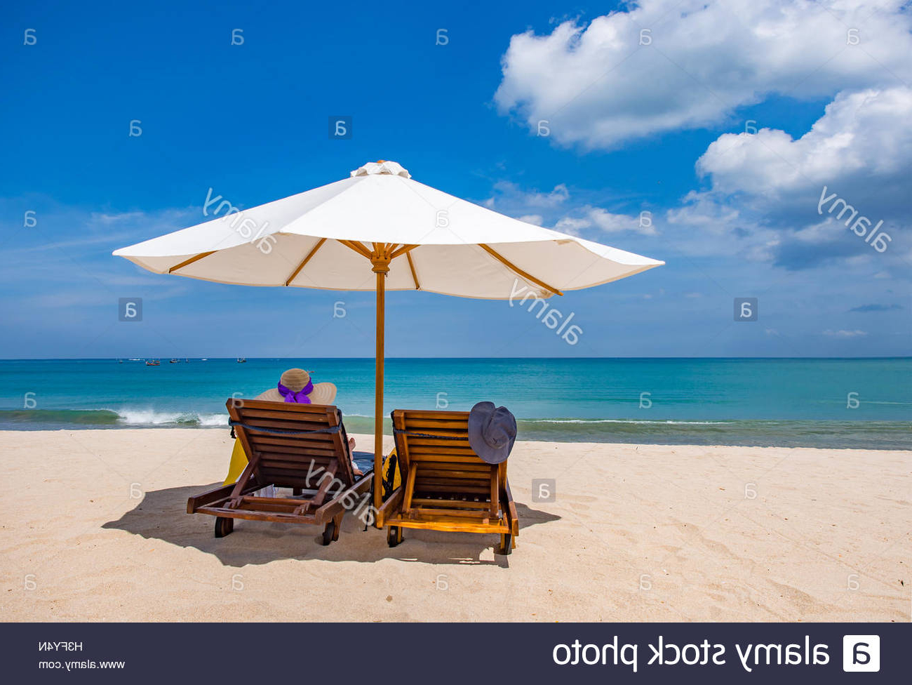 Popular Seaside Beach Umbrellas In Woman Resting Under A Beach Umbrella Facing The Seaside In A (View 6 of 20)