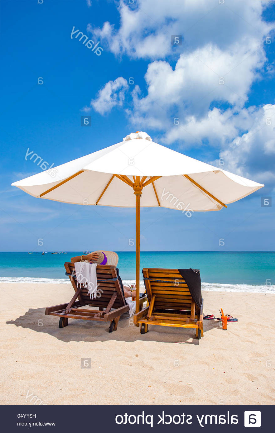 Seaside Beach Umbrellas Intended For Most Recent Woman Resting Under A Beach Umbrella Facing The Seaside In A (View 13 of 20)